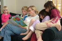 _mother_reading_a_book_to_kids.jpg